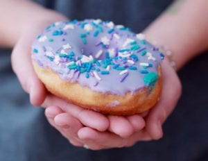 Person holding donut with caption: As you ramble through life, brother Whatever your goal, Keep your eye upon the doughnut, And not upon the hole. [the optimist's creed]